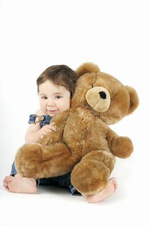 infancy: A sweet baby girl hugs her teddy and smiles
