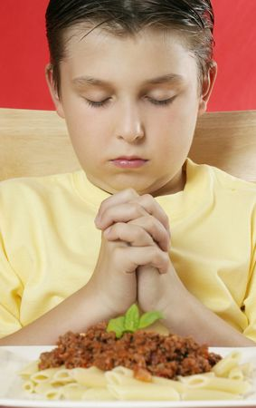 A boy with hands clasped giving thanks before a meal photo