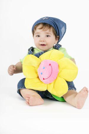bandana girl: Country Bumpkin - Un b�b� dans un denim outfit d�tient un sourire jaune tissu fleur.  Banque d'images