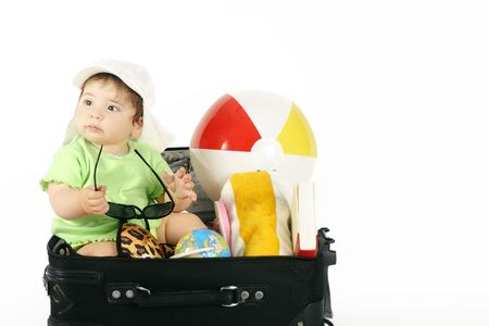 packing suitcase: Summer Holiday - Baby sitting in a bag packed with beachy things. Stock Photo