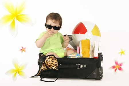 jetset: Escape to the tropics.    A baby sitting in a small suitcase packed with beachy things.   Frangipani decorations can be removed if you like or duplicated with paths embedded.. Stock Photo