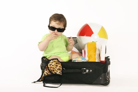 Island Getaway.    A baby sitting in a small suitcase packed with beachy things. Stock Photo