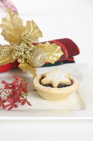 carne picada: Tarta de fruta picada en un plato adornado con arbustos y Navidad australiana servilleta. Foto de archivo