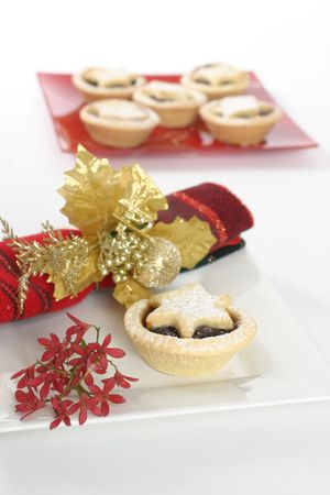 minced pie: Sweet fruit mince pies.   Red Australian Christmas bush decorative napkin.  Focus on foreground.