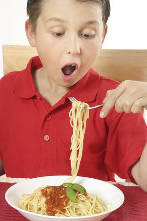 Boy with spaghetti noodles and tomato based sauce. photo