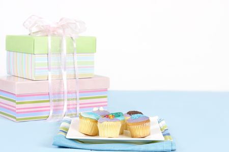 pink satin: Miniature cakes sitting on a white plate on a blue tablecloth.  Pastel boxes tied with pale pink satin and gauze ribbon in backgound.  Focus is to the foreground and cakes only.  Space for a message.