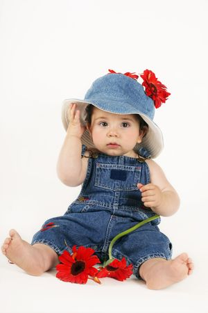 Country Girl in Denim - Beautiful young baby girl wearing denim overalls and sunhat is sitting amongst red gerbera daisies.