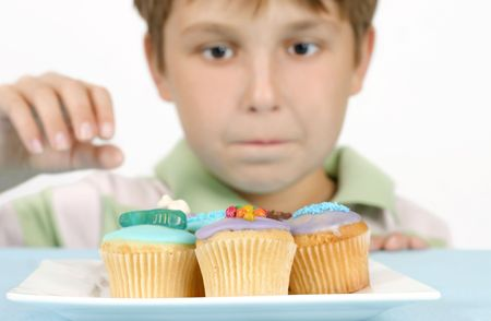 Yummy Cakes - This photo shows a boy eyeing off some cakes.  He has his hand outstretched to take one.    The focus is to the cakes.