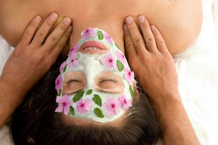 enjoys: Peace and Puritry - A woman enjoys a therapeutic neck massage during a facial treatment - landscape Stock Photo