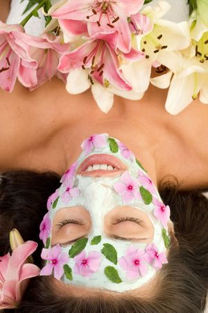 Floral Beauty - Woman with a botanical mask and flowers decoration Stock Photo
