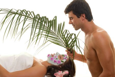 indulgence: Indulgence - A young woman is gently fanned with a palm frond at a day spa or exotic beauty salon or perhaps she is pampered by her husband or lover Stock Photo
