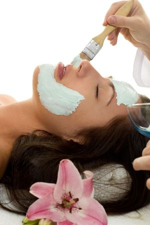 A beautician applying a facial treatment mask