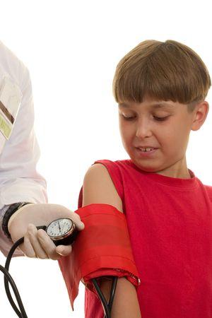 causaba: Un doctor usando un pun�o del punto de ebullici�n (sphygmomanometer) para tomar la presi�n arterial de un ni�o. La presi�n arterial se mide en t�rminos de mil�metros del mercurio (mmHg). La tensi�n arterial alta en ni�os se puede causar por otras enfermedades -- enfermedad generalmente del coraz�n o del ri��n. Foto de archivo