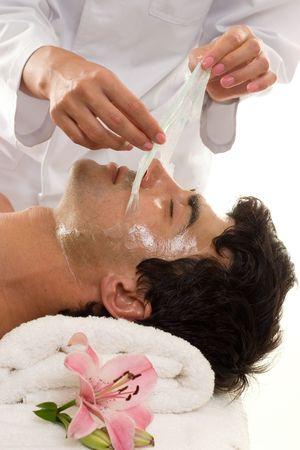 esthetician: Facial Peel - A beautician performs a facial peel on a male client.