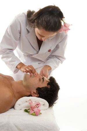 Beautician or esthetician treating a male client Stock Photo