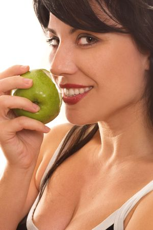 A beautiful smiling woman eating a fresh green apple. eg - health, diet, nutrition, sin, temptation, etc... photo