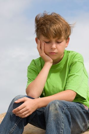 ni�os tristes: Pensamientos solemnes - una sentada y un pensamiento abatidos del ni�o. Foto de archivo