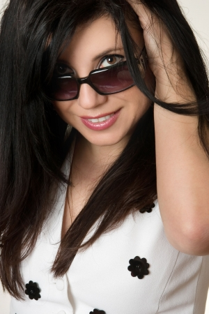 coy: Got the Look?.  Beautiful young woman looking over the top of her sunglasses. eg, beauty, style, optomestrists, fashion accessories, designer looks... Stock Photo
