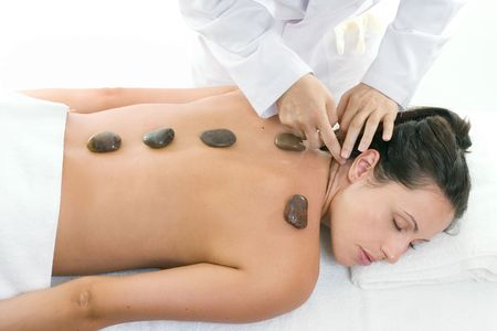 rejuvenate: A female receiving massage and hot rock treatment to back and neck at a beauty salon or day spa facility. Stock Photo