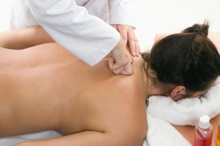 tejido: Una mujer recibe un masaje profundo del tejido fino con el amasamiento. El amasamiento es una t�cnica del masaje en la categor�a de los movimientos del petrissage