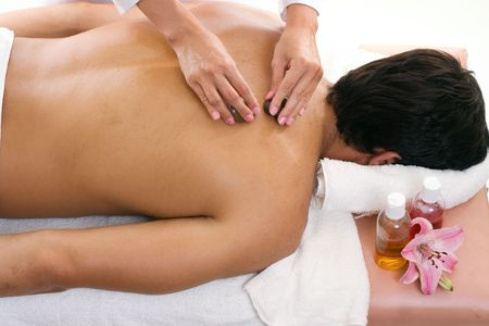 Thermal Stone Massage therapy. The therapist applies oil to the skin and then glides warmed stones across the body�s meridian lines. The heated stones melt away tension as each rock is massaged deep into sore, fatigue muscles. Stock Photo
