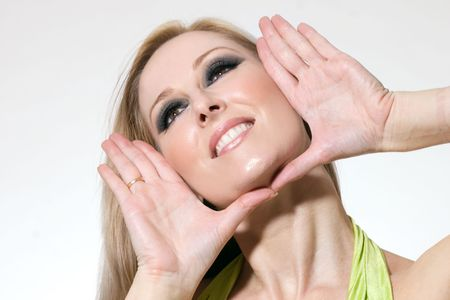 poised: Smiling blonde female wearing makeup with hands poised in a face frame.