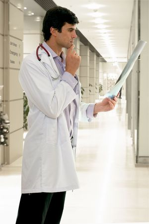 oncologist: Concerned male doctor analyzing a medical x-ray in a hospital.