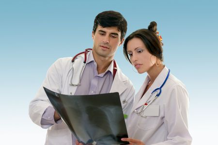 confer: Male and female doctors confer over the results of a patient chest x-ray.