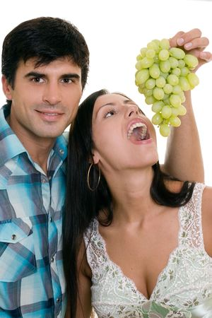 Adult couple playfully eating grapes photo