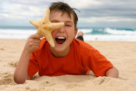 ecstatic: Ecstatic child lying on the beach holding a starfish to face.