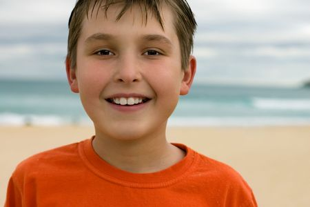 Smiling boy with a soft beach background. photo