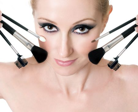 Makeup brushes and tools help achieve flawless application of cosmetics.  Brushes and applicators surround a womans face. Stock Photo