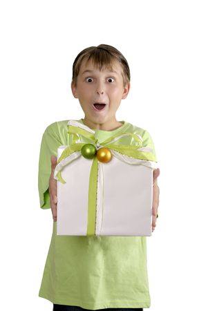 whitespace: Excited wide eyed boy holding a present wrapped with green white and gold ribbon and finished with green and gold baubles. Stock Photo