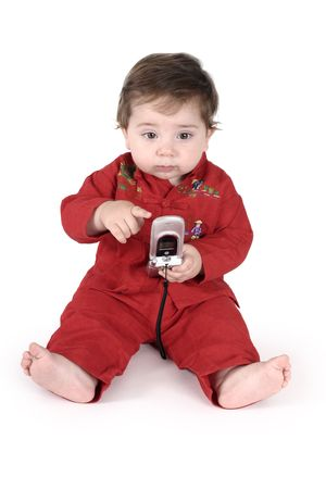 Its easy to stay in touch - a young toddler sitting on floor holding a mobile phone. photo