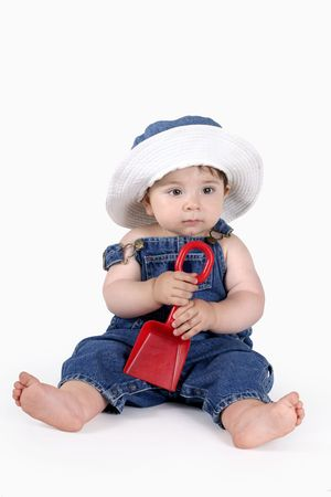 sunhat: Baby dressed in denim overalls and matching sunhat holding a spade