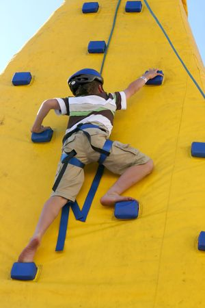 ni�o escalando: Un ni�o �gil joven sube una pared. Un cierto movimiento leve. Foto de archivo