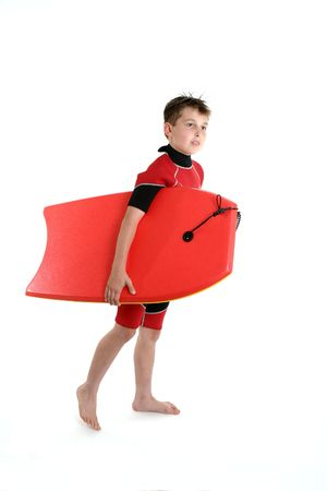 bodyboarder: A boy carrying a bodyboard dressed in wetsuit ready for some summer fun. Stock Photo