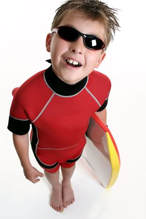bodyboarder: A child dressed in wetsuit and holding a board, is ready for the beach,
