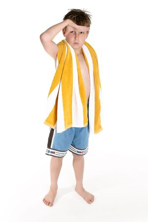 board shorts: Boy in board shorts and beach towel slung over shoulder looks out to the surf or pool.