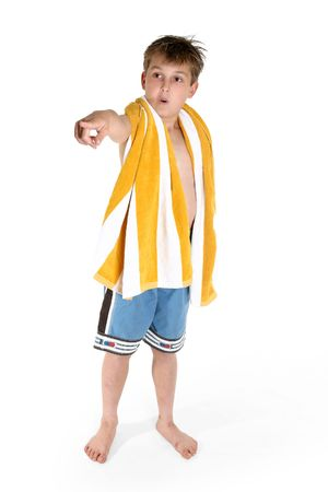 awe: A young curious boy dressed in board shorts and beach towel around shoulders points his finger with a wide eyes expression of awe or wonder.