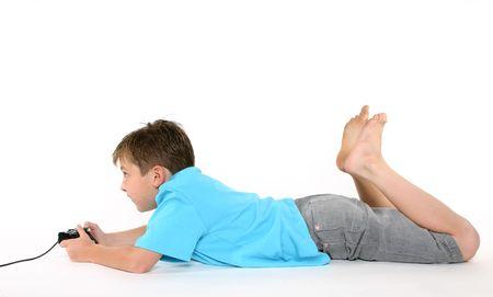 chłopięctwo: Casually ubrane dziecko leżące na podłodze grać w gry komputerowe Zdjęcie Seryjne