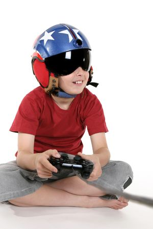 engrossed: Child wearing a helicopter pilot helmet with visor happily plays a flight simulator computer game. Stock Photo
