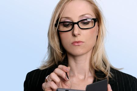 electronic organiser: A businesswoman using her electronic organiser. Stock Photo