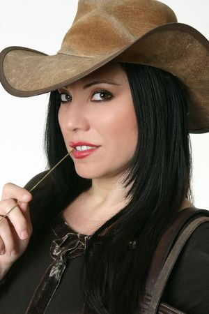 Country girl wearing leather hat and chewing on some long grass. photo