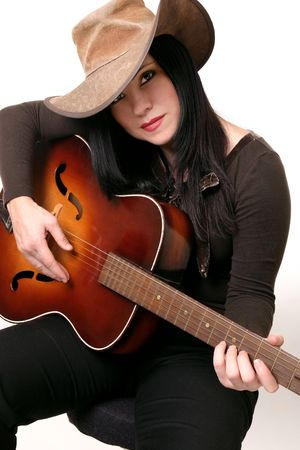A woman sitting on a stool, playing an acoustic guitar Stock Photo