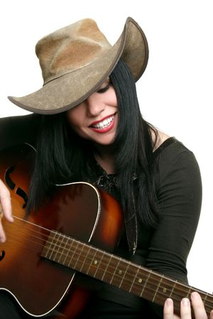 akubra: Country musician happily playing her acoustic guitar.  Some motion in fingers and strings.