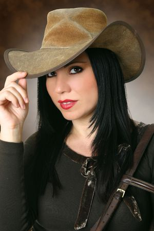 Country cowgirl in casual clothing wearing a well worn leather  hat. Stock Photo
