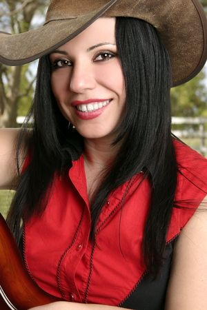 An attractive smiling female against a lovely country ranch setting.