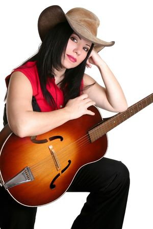 A woman in western clothing rests casually with a guitar.