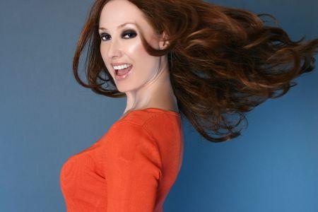 highlighted hair: Una donna carefree che fila e che flicking verso lesterno i suoi capelli lunghi evidenziati biondi marroni scuri della fragola ed auburn. Alcune parti nel movimento.